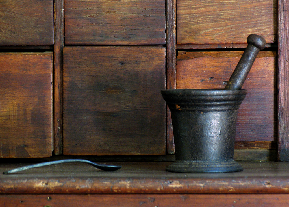 mortar and pestal with metal spoon in front of wood wall