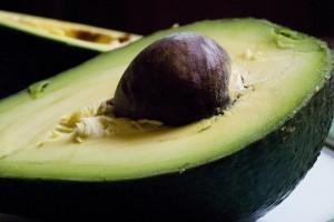 organic avocado split to show pit where avocado oil comes from.
