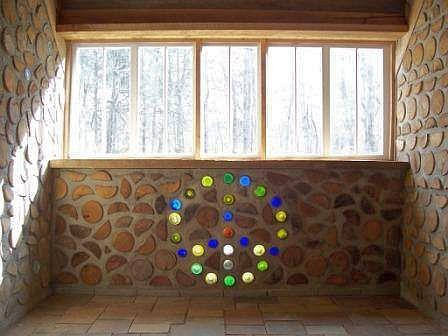 Recycled bottle peace sign in a cordwood wall.